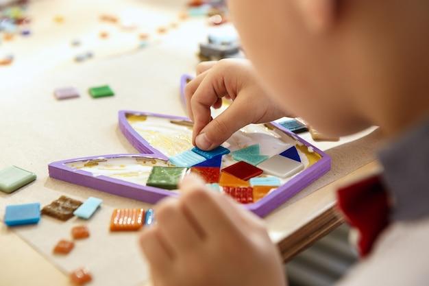 A arte do puzzle em mosaico para crianças, um jogo criativo para crianças. as mãos estão jogando mosaico na mesa. detalhes coloridos multicoloridos close-up. criatividade, desenvolvimento infantil e conceito de aprendizagem