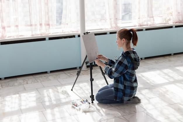 A artista jovem mulher adolescente está sentada no chão de azulejos de mármore. mulher em processo de pintura com tintas a óleo.