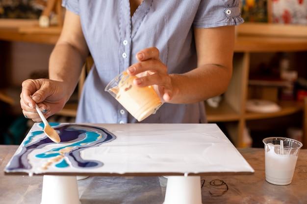 A artista segura o copo de tinta na mão esquerda e a colher na direita, com a qual aplica tinta na tela. masterclass. criatividade e design. o artista em ação. liberdade e inspiração.