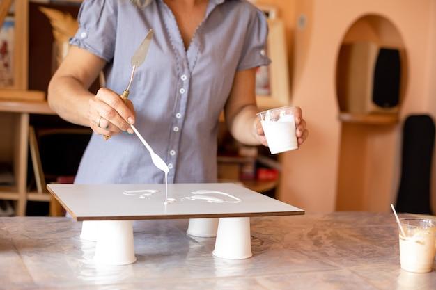 A artista segura um copo de tinta branca com a esquerda e com a mão direita aplica tinta na superfície para criar um fundo branco. criatividade e design. liberdade e inspiração. hobbies e artesanato.