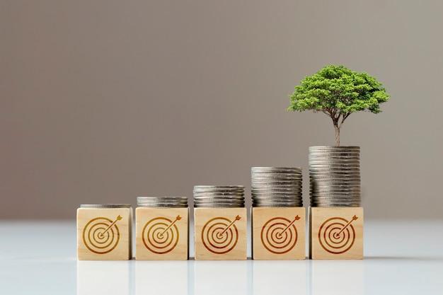 A árvore cresce a partir da moeda que está no bloco quadrado de madeira e o ícone do objetivo, o conceito de objetivo financeiro e o sucesso financeiro.