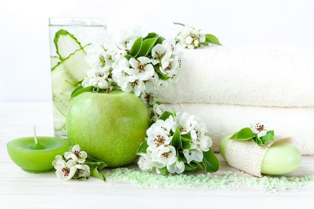 A árvore de maçã de florescência floresce, bebida fria, maçã verde, sal aromático do mar, vela e toalhas.