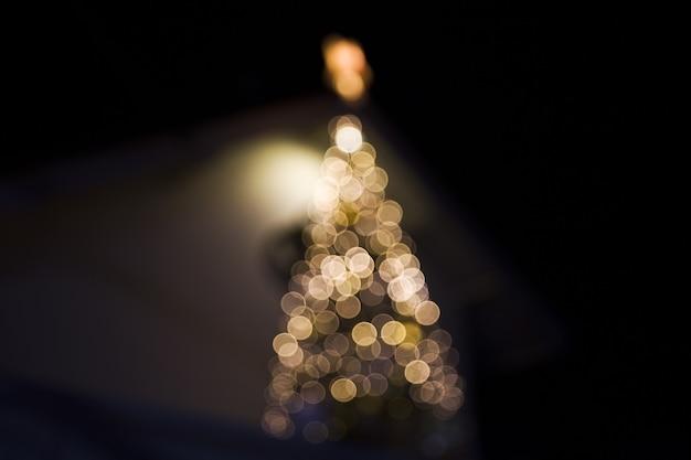 A árvore de natal borrou as luzes fechadas para abrigar o conceito festivo