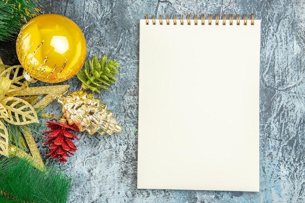 A árvore de natal brinca com um caderno na superfície cinza