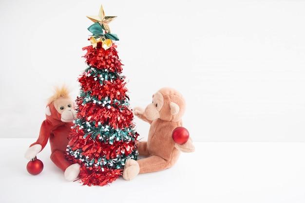 A árvore de natal com macaco dos pares e decoram felizmente a sensação no ano novo.