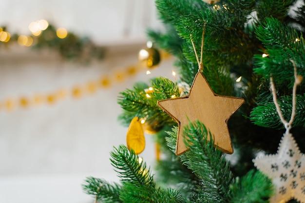 A árvore de natal é decorada com brinquedos, bolas douradas, ovos brancos e guirlandas em close-up.