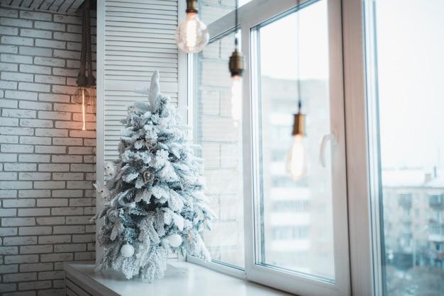 A árvore de natal na neve está na janela.