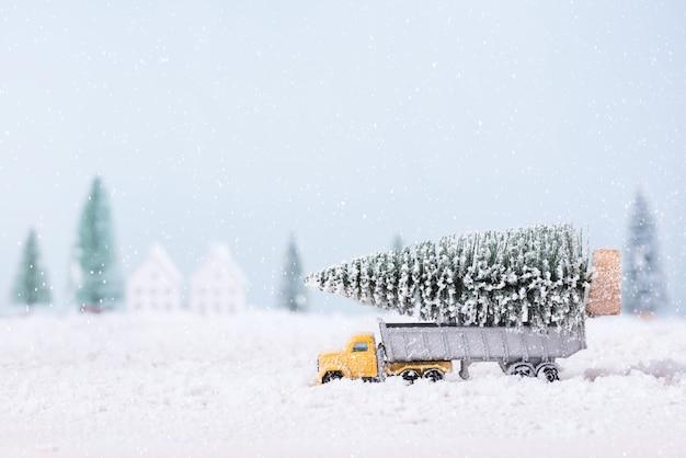A árvore de natal no caminhão do carro de brinquedo estava correndo pela neve no campo do fundo da paisagem natural.