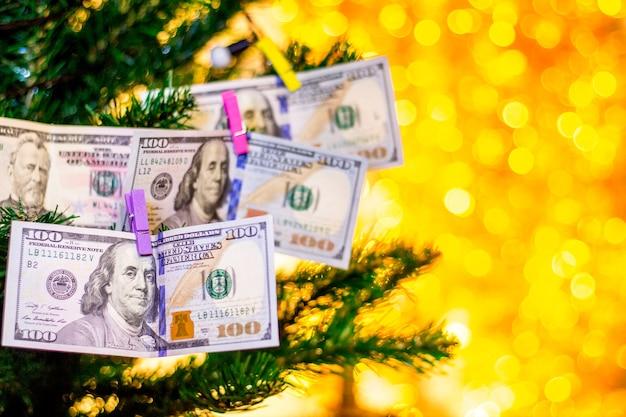 A árvore de natal no escritório é decorada com notas de dólar_