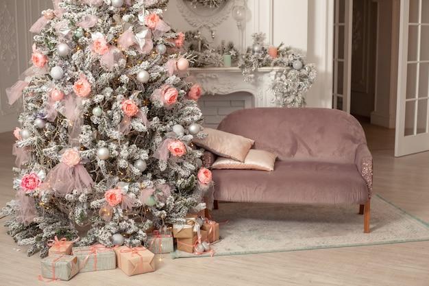 A árvore de natal no quarto perto da lareira