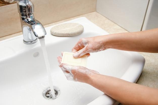 A as mãos com sabão são lavadas na torneira com água. limpo de infecção, sujeira e vírus. em casa ou no consultório de ablução do hospital.