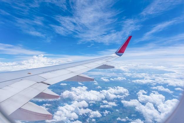 A asa de um voo do avião acima das nuvens olha da janela de cabine.