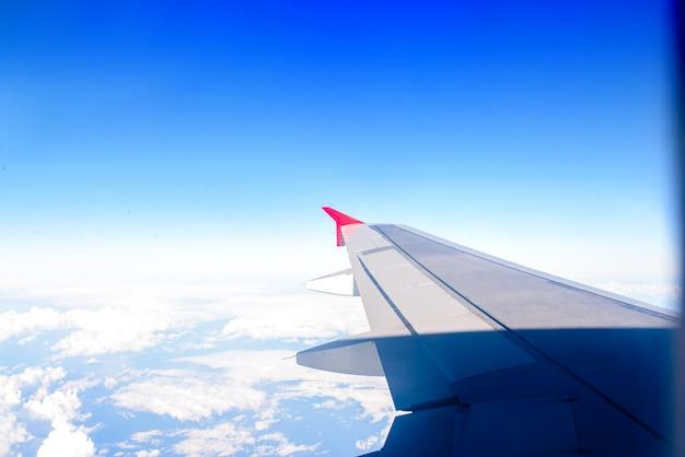 A asa do avião contra o céu. o conceito de viagens e vôos.