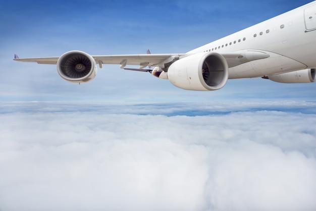 A asa e o motor do avião de passageiro estão voando no céu.