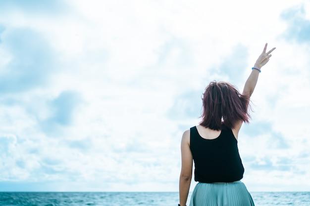A ascensão da mulher entrega até o conceito da liberdade do céu com céu azul.