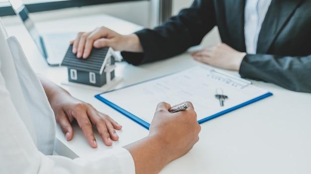 A assinatura manual do contrato depois que o corretor imobiliário explica o contrato comercial, o aluguel, a compra, a hipoteca, um empréstimo ou o seguro da casa ao comprador.