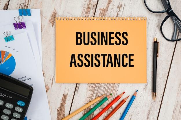 A assistência empresarial está escrita em um bloco de notas em uma mesa de escritório com acessórios de escritório.