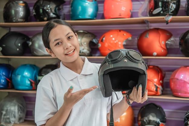 A assistente de loja sorri com gestos com as mãos para oferecer algo enquanto segura um capacete em uma loja de capacetes