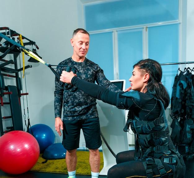 A atleta feminina que eles exercitam em um estúdio de fitness ems