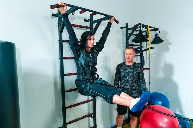 A atleta feminina que eles exercitam em um estúdio de fitness