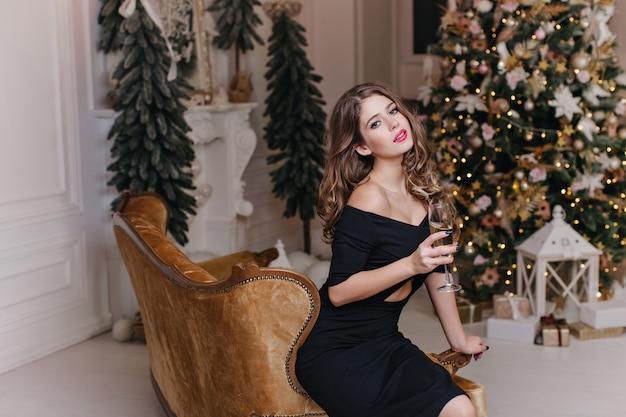 A atmosfera elegante e cara de ano novo no apartamento contribui para o maravilhoso humor da morena elegante e atraente com lábios brilhantes, segurando uma taça de vinho espumante