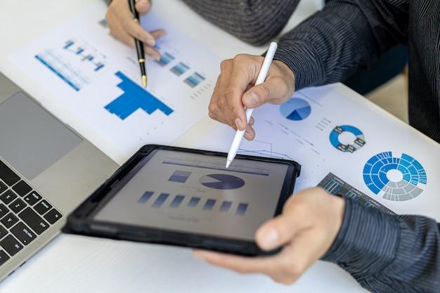 A atmosfera na sala de conferências contou com a presença de dois empresários, uma reunião de brainstorming operacional da empresa conjunta para o crescimento dos negócios, eles estão olhando os dados do tablet.