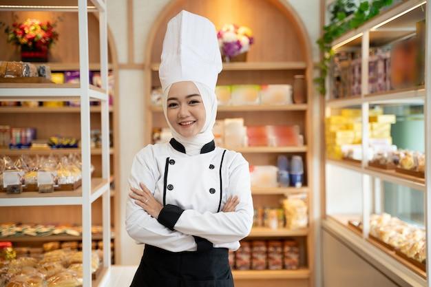 A atraente baker muçulmana sorrindo para a câmera enquanto está em sua loja