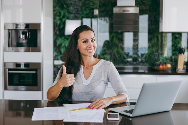 A atraente jovem mulher de negócios moderna mostra um gesto legal com os polegares e trabalha com documentos e laptop na cozinha de casa