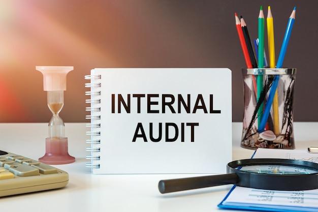 A auditoria interna é escrita em um caderno sobre uma mesa de escritório com material de escritório.