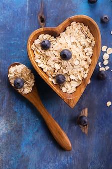 A aveia crua lasca-se com o mirtilo fresco na bacia de madeira dada forma coração no fundo rústico azul.