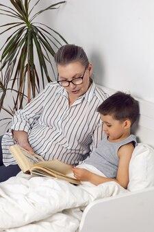 A avó de óculos e camisa branca lê um livro para o neto deitado na cama em um quarto infantil branco