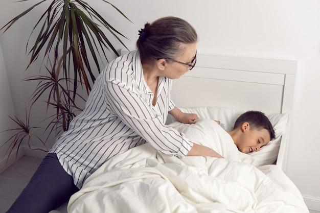A avó de óculos e camisa branca lê um livro para o neto deitado na cama