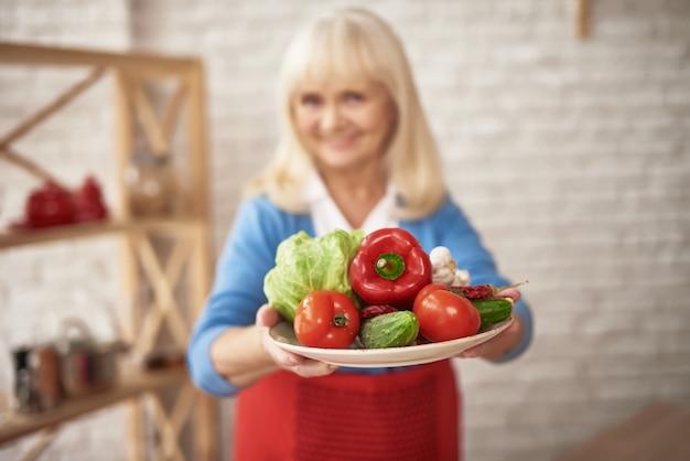 A avó de sorriso guarda vegetais frescos cultivados em casa.
