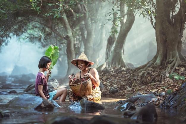 A avó e a neta asiáticas travam o caranguejo em uma cesta em um córrego em tailândia.