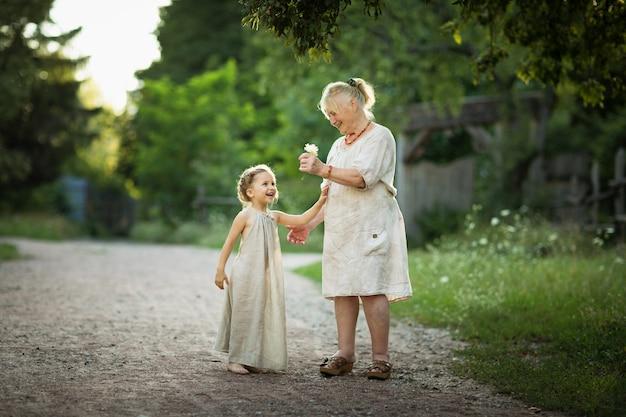 A avó e a neta caminham pelo parque com roupas vintage brancas