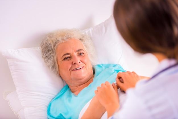 A avó idosa encontra-se na cama na clínica.