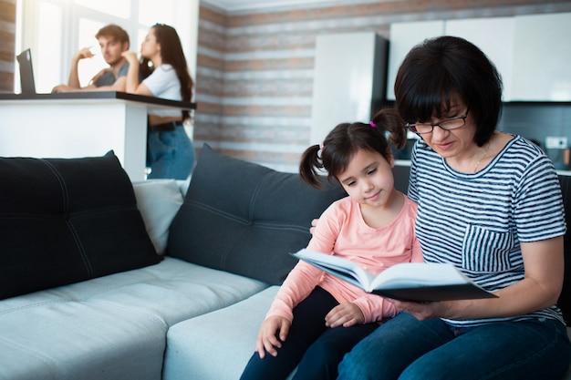 A avó lê um livro para a neta. pai e mãe usam laptop no fundo. grande família em casa.