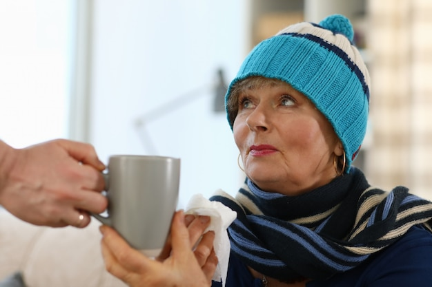 A avó se senta no sofá e segura uma xícara