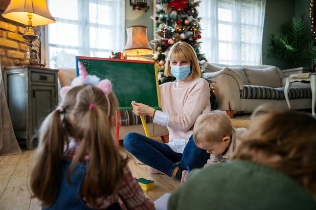 A babá e crianças com máscara facial por causa de covid-19 e coronavírus na pré-escola