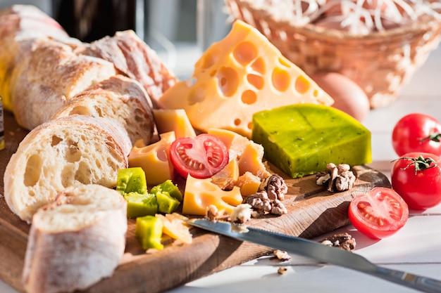 A baguete e queijo no fundo de madeira