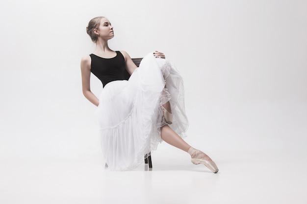 A bailarina adolescente no bloco branco, sentado na cadeira