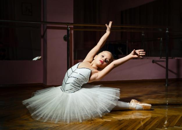 A bailarina bonita com coque coletou o cabelo usando vestido branco e sapatilhas com as mãos levantadas, sentado no chão de madeira.