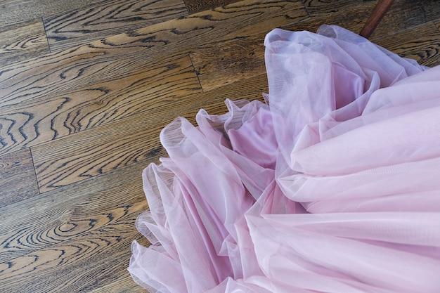 A bainha do elegante vestido de noiva rosa no chão de madeira.