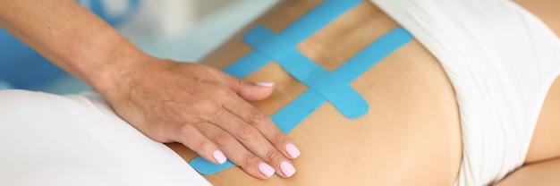 A bandagem kinesio nas costas é um método eficaz de tratar a escoliose e a dor na clínica com faixas elásticas.