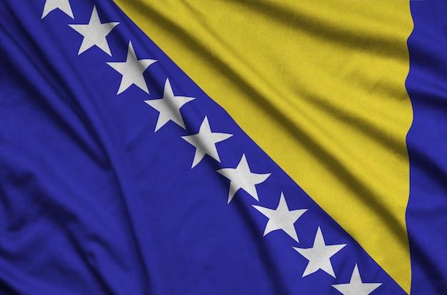 A bandeira da bósnia e herzegovina é retratada em um tecido esportivo com muitas dobras.