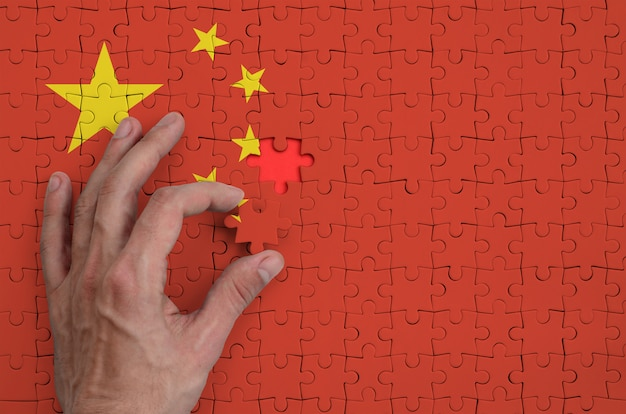 A bandeira da china é retratada em um quebra-cabeça, que a mão do homem completa para dobrar