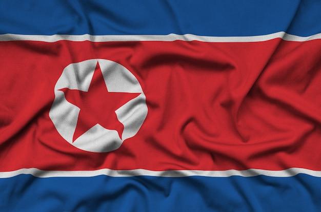 A bandeira da coréia do norte é retratada em um tecido esportivo com muitas dobras.