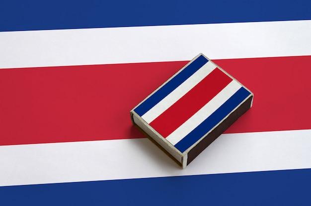 A bandeira da costa rica é mostrada em uma caixa de fósforos que fica em uma bandeira grande