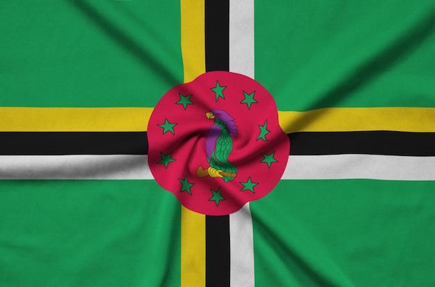 A bandeira da dominica é retratada em um tecido esportivo com muitas dobras.