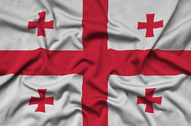 A bandeira da geórgia é retratada em um tecido esportivo com muitas dobras.